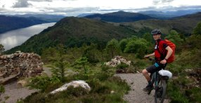Riding a mountain bike on the Great Glen Way above Loch Ness, Scotland UK